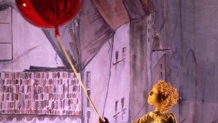 Colour image of a puppet boy holding a red balloon in the staging of The Red Balloon at Longfield Hall