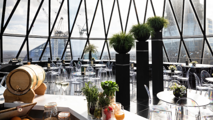 The Gherkin bar during the daytime, with views of London's skyline and cocktails on the bar.