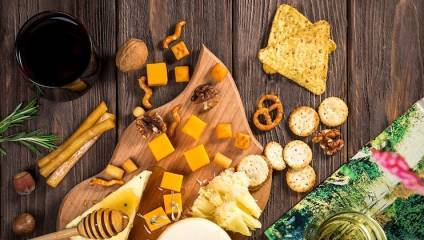 Flat lay of a cheese board with biscuits and wine on a wooden surface